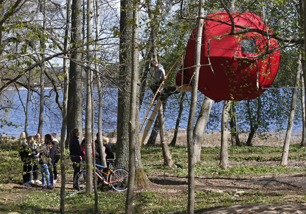 Kids climbing up to red Tree Tent