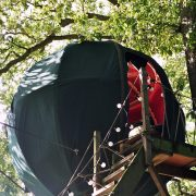 The Secret Campsite woodland Tree Tent with wooden steps leading up to the red interior