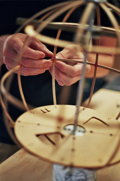 Hands making a scale model of the Tree Tent glamping pod